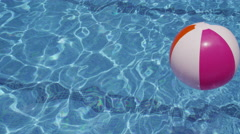 Colorful beach ball floating in pool Stock Footage