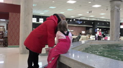 Mother and daughter talk near Fountain exchanging impressions - stock footage