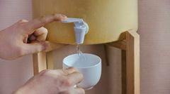 Pouring white cup with water from dispenser Stock Footage