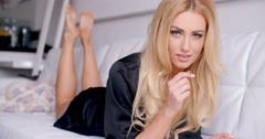 Blond Woman in Black Nightwear Lying on Couch Stock Footage