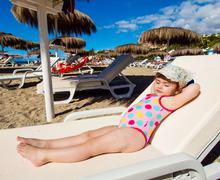 Adorable baby girl sunbathing on a deck chair on the beach Stock Photos