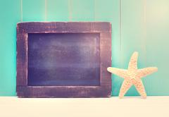 Starfish and small chalkboard on a teal colored wooden background - stock photo