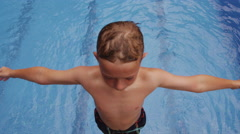 Boy falling into pool, slow motion Stock Footage