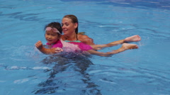 Mother teaching daughter to swim in pool - stock footage