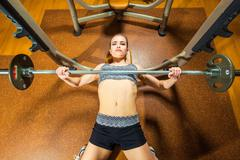 Sports young woman doing exercises with barbell on bench in the gym. Bar Bench Stock Photos