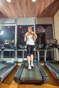 Pretty girl working out in a treadmill at the gym and smiling - stock photo