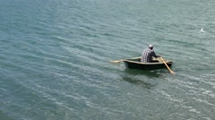 Man row a row boat at sea - stock footage