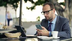 Young businessman comparing data on smartphone and laptop in cafe city HD Stock Footage