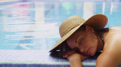 Woman laying by pool Stock Footage
