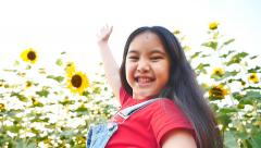 Slow motion of little Asian child playing in the sunflower field Stock Footage
