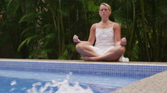 Woman meditating by pool Stock Footage