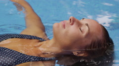 Woman floating and relaxing in pool Stock Footage