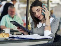 Businesswoman talking on cellphone and comparing data on tablet and documentNTSC Stock Footage