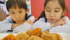Slow motion of Happy Asian girls with fried chicken in restaurant, Tilt up - stock footage