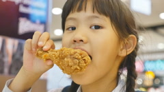 Asian child enjoys eating fried chicken Stock Footage