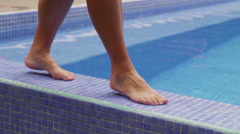 Closeup of feet walking by pool and dipping toe in water Stock Footage