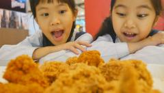 Slow motion of Happy Asian girls with fried chicken in restaurant Stock Footage