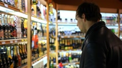 Man choosing products in alcoholic during weekly shopping at supermarket store Stock Footage