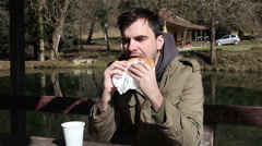 Male sitting, eating and drinking. Man eating fast food. Hamburger or sandwich. Stock Footage