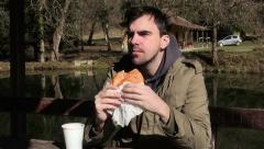 Man eating hamburger and drinking water in park. Fast food. Sandwich. Obesity. Stock Footage