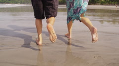 Couple running on beach, closeup of feet, slow motion - stock footage