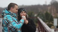 Stock Video Footage of young couple eating hotdog after skiing
