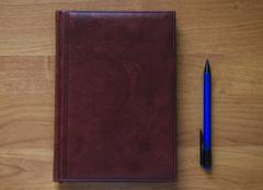 Notepad and pen on wood office table - stock photo