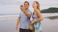 Couple taking photo together at beach, Costa Rica Stock Footage