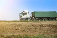 Dump truck goes on the country highway Stock Photos