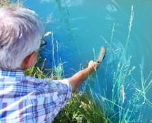 Fisherman releasing hooked fish Stock Photos
