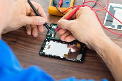 Close-up Of Technician Repairing Cellphone With Multimeter On Desk Stock Photos