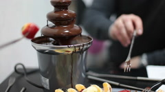 Chocolate fountain and human hands with fork eating strawberry, close-up - stock footage