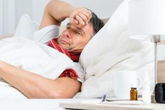 Stock Photo of Sick Mature Man Lying On Bed In Bedroom