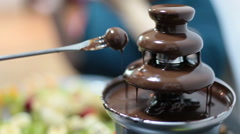 Chocolate fountain and human hand with fork eating grapes, copyspace, close-up - stock footage