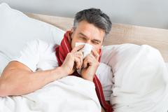 Sick Mature Man Blowing His Nose While Lying On Bed At Home Stock Photos