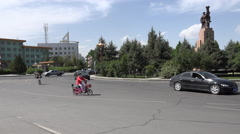 Midday traffic at roundabout with industrial statue, Jiayuguan Stock Footage