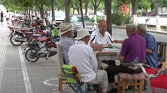 Men playing Mahjong on sidewalk wide shot, Jiayuguan Stock Footage