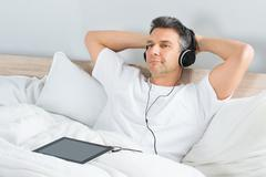 Relaxed Mature Man Listening Music On Headphone Attached To His Tablet Stock Photos