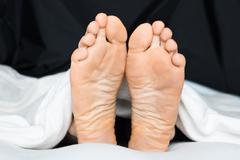 Close-up Of A Person's Feet Under The Blanket On Bed Stock Photos