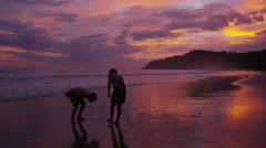 Two boys running on beach at sunset, Costa Rica Stock Footage