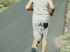 Man jogging up through road NTSC Stock Footage
