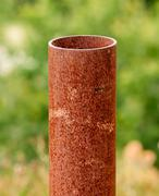 Vertical rusted metal pipe on green - stock photo