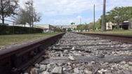 Stock Video Footage of Lowe Angle Close Up Tracking Shot Train Tracks With Freeway In Distance