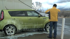 Man Rinsing Off Car WS Stock Footage