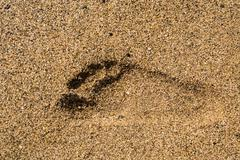 Single right foot print in sand - stock photo