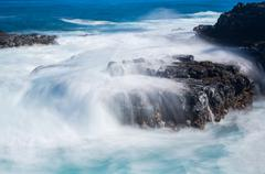 Raging sea flows over lave rocks on shore line - stock photo