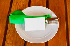Dishware and blank paper card on table in restaurant - stock photo