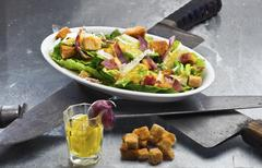 Caesar salad - original version with egg dressing and crunchy bacon topping Stock Photos