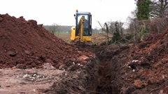 Mini digger excavating a trench Stock Footage