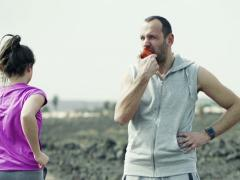 Man eating apple and woman jogging on desert NTSC Stock Footage